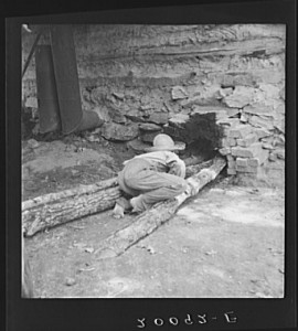 Ten year old son of tobacco tenant tends the fire which is curing the tobacco in the barn. Granville County, North Carolina