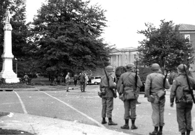 Several armed men in uniform on the campus of the University of Mississippi, October 1, 1962. The men were part of the law enforcement effort to restore and maintain order on the campus during the riots that occurred after the integration of the university by James Meredith in late September. The Confederate monument in question is at left. (Special Collections, McCain Library and Archives, University of Southern Mississippi.)