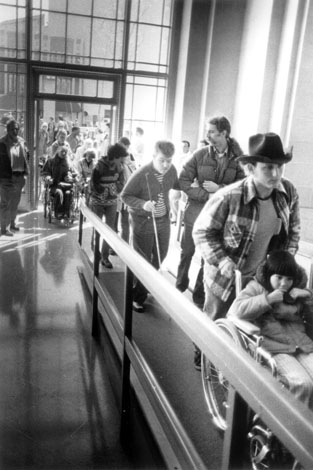 Demonstrators enter San Francisco's regional headquarters of the Department of Health, Education and Welfare for a 1977 sit-in to protest the government's failure to publish regulations for accommodations or to punish institutions that refused to comply with the Section 504 Rehabilitation Act of 1973.